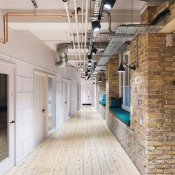 Corridor space with original exposed brick, wood flooring and several phone booths.