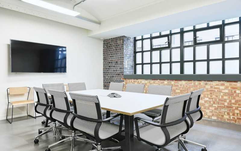Meeting room with exposed brickwork and conference calling facilities and TV Screen for companies to use at this office space in The Embassy Tea House on Union Street.